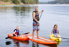 Attractive family kayaking and paddle boarding together on a beautiful lake. Attractive young family kayaking and paddle boarding together on a beautiful lake royalty free stock photos