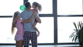 Attractive family in love embrace by the window stock video footage
