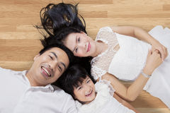 Attractive family lying on wooden floor. Unique perspective of Asian family smiling at the camera while lying down on the wooden floor at home Royalty Free Stock Photo