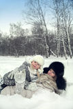 Attractive family mother and daughter lay on a snow in a winter park. Look to camera Royalty Free Stock Image
