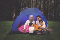 Family play guitar in camping tent at forest. Attractive family playing a guitar in a camping tent at the forest. Shot outdoors stock photography