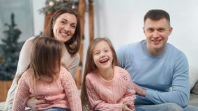 Attractive family posing with Christmas decoration at home laughing looking at camera