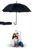 Attractive family sitting under umbrella in studio. Portrait of joyful parents and their daughter sitting in the studio under umbrella. Life and family insurance Stock Photography