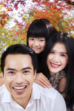 Attractive family smiling under autumn tree Stock Photos