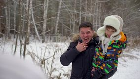 Attractive family of three having fun in a snow winter park. Father and son playing outside on winter day. Man throws stock video