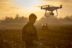 Farmer navigating drone above farmland. Attractive farmer navigating drone above farmland. High technology innovations for increasing productivity in agriculture royalty free stock image