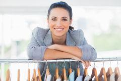 Attractive fashion designer leaning on clothes Royalty Free Stock Photos