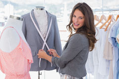 Attractive fashion designer measuring blazer Royalty Free Stock Image