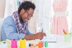 Attractive fashion designer sitting at his desk drawing Stock Photo