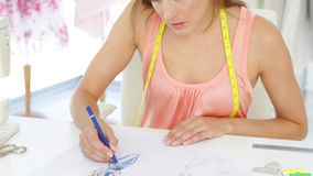 Attractive fashion designer sketching a design Stock Photography