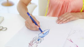 Attractive fashion designer sketching a dress design Royalty Free Stock Image