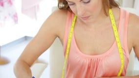 Attractive fashion designer sketching a dress design stock video