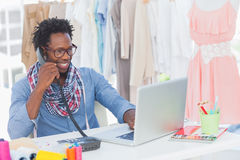 Attractive fashion designer speaking on the phone. In a creative office Royalty Free Stock Photos
