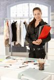 Attractive fashion designer standing by desk stock image