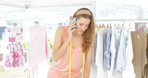 Attractive fashion designer talking on the phone stock video