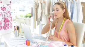 Attractive fashion designer working on laptop and answering the phone stock footage