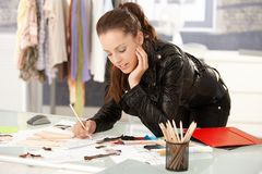 Attractive fashion designer working in studio royalty free stock images