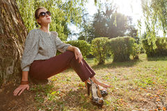 Attractive fashion girl in park. Wearing sun glasses and resting against a tree Royalty Free Stock Images