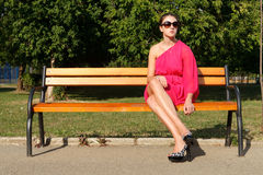 Attractive fashion girl in park. Attractive fashion girl wearing pink dress in park wearing sun glasses and resting on a bench Stock Photo