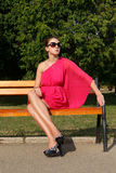 Attractive fashion girl in park. Attractive fashion girl wearing pink dress in park wearing sun glasses and resting on a bench Stock Photography