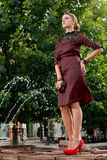 Attractive fashion girl in town. Standing on fountain Stock Images