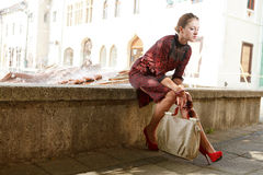 Attractive fashion girl in town. Sitting on fountain thinking and holding a hand bag Royalty Free Stock Photography