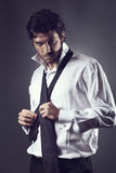 Attractive fashion model wearing tie. And looking at camera. Fashion or businessman concept Stock Photos