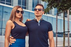 Attractive fashionable couple, blonde girl and handsome man standing in the modern city against a skyscraper. An attractive fashionable couple, blonde girl and stock images