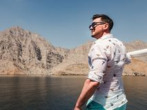 Attractive, fashionable man standing on a boat stock photo
