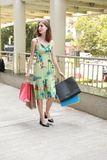 Attractive fashionable shopping girl on the street with colorful shopping bags. Let s go shopping, glamorous fashion lady royalty free stock image