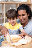 Attractive father helping his son cut some bread. In the kitchen Royalty Free Stock Photos