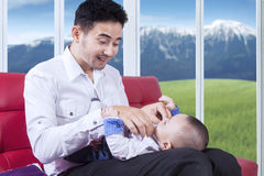 Attractive father replace his baby wear Stock Photography