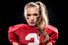 Attractive female american football player. Close-up portrait of attractive female american football player in uniform looking at camera on black Stock Images