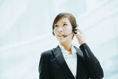 Attractive female Asian businesswoman wearing a headphones with microphone Stock Photos
