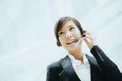 Attractive female Asian businesswoman wearing a headphones with microphone Stock Photography