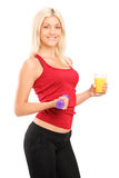 Attractive female athlete holding a dumbbell and glass of juice Stock Photos