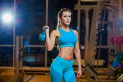 Attractive female athlete performing a kettlebell in gym. stock images
