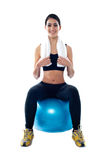 Attractive female athlete sitting on blue ball Royalty Free Stock Images