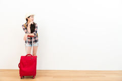 Attractive female backpacker leaning on suitcase Stock Photos