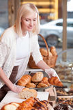 Attractive female baker is selling sweet pastry Royalty Free Stock Photos