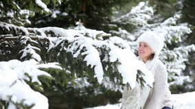 Attractive female beats the fir-tree`s branch and shakes off a snow stock video footage