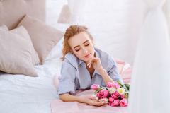 Attractive female in the bedroom. Attractive female resting on the bed in the light bedroom stock images