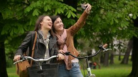 Attractive Female Bicyclists are Photographing Themselves Using Smartphone Outdoors in the Park During Spring Time. Two. Attractive Female Bicyclists with Long stock video