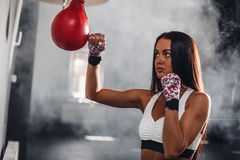 Attractive female boxer at training with boxing pear. Sexy strong woman on background boxing gym Royalty Free Stock Photography