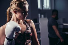 Female Boxer wearing gloves posing in boxing studio. Attractive Female Boxer wearing gloves posing in boxing studio Royalty Free Stock Image
