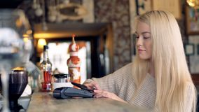 Attractive female at cafe making online payment using smartphone. 4K. Customer hand making online payment using smartphone stock footage
