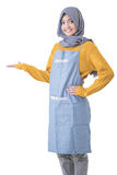 Attractive female cafe worker with hijab presenting to copyspace Royalty Free Stock Images