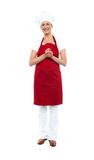 Attractive female chef in red apron and toque Royalty Free Stock Image