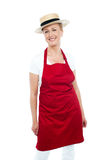 Attractive female chef wearing red apron and hat Stock Photos