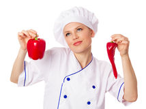 Attractive female cook in professional uniform holding natural red peppers, confused Royalty Free Stock Photo